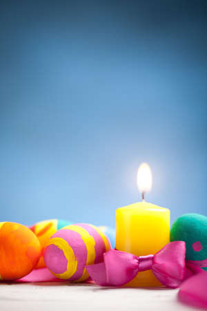 Colorful easter eggs and candle with blurred blue background. At the top of image is empty space to put text or something else. This file is cleaned and retouched.