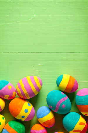 Colorful easter eggs on green wooden table. At the top of image is empty space to put text or something else. This file is cleaned and retouched.