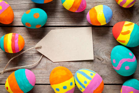 Colorful easter eggs with blank note on old wooden table. In center is empty space to put text or something else. This file is cleaned and retouched. 版權商用圖片