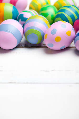 Colorful easter eggs on white wooden table. On bottom is empty space to put text or something else. This file is cleaned and retouched.