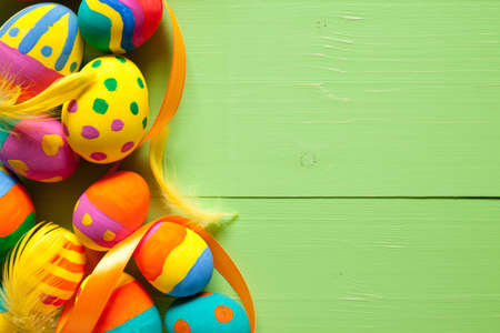 Colorful easter eggs on green wooden table. On the right is empty space to put text or something else. This file is cleaned and retouched.