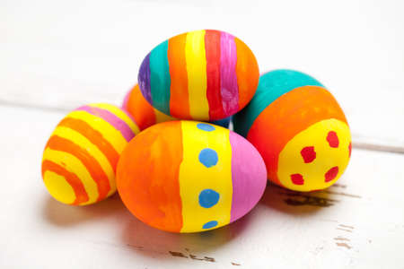 Close up of colorful easter eggs on white table. This file is cleaned and retouched.