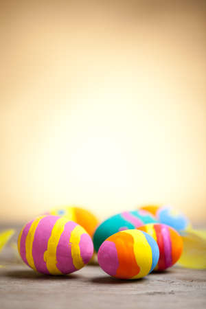 Colorful easter eggs on wooden table with blurred yellow background. At the top of image is empty space to put text or something else. This file is cleaned and retouched. 版權商用圖片