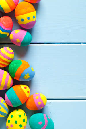 Colorful easter eggs on blue wooden table. On the right is empty space to put text or something else. This file is cleaned and retouched.