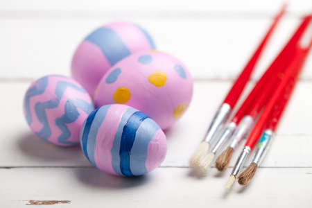 Colorful easter eggs with paintbrush on white wooden table. This file is cleaned and retouched.