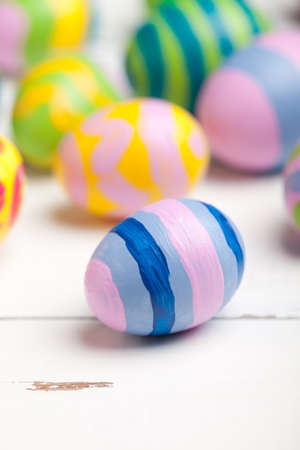 Colorful easter eggs on white wooden table. This file is cleaned and retouched. 版權商用圖片