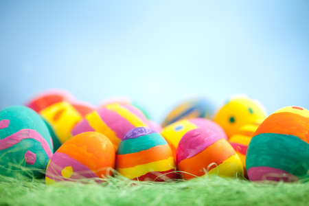 Colorful easter egg with dry green grass on blurred blue background. At the top of image is empty space to put text or something else. This file is cleaned and retouched. 版權商用圖片
