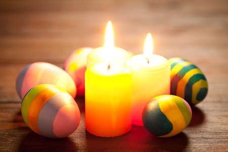 Colorful easter eggs and candles on old wooden table. This file is cleaned and retouched.