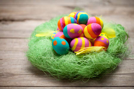 Colorful easter eggs with yellow feather and green grass nest on old wooden table. This file is cleaned and retouched.