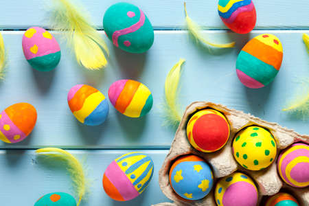 Colorful easter eggs in box on blue wooden table. This file is cleaned and retouched.