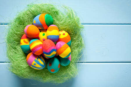 Colorful easter eggs with green grass nest on blue table. On the right side is empty space to put text or something else. This file is cleaned and retouched.