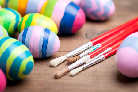Colorful easter eggs with paintbrush on old wooden table. This file is cleaned and retouched.