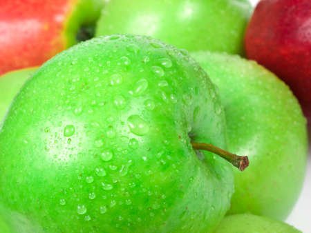 fresh green and red apples with water drops on white background