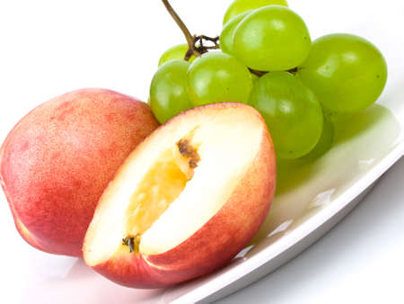 fresh nectarines and bunch of grapes on white plate
