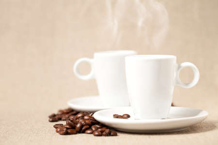 Small coffee cups with hot esspresso on linen background. This file is cleaned and retouched.