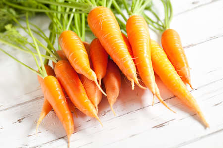 Close up of natural carrots on old white table. This file is cleaned and retouched.