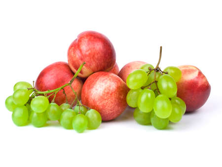 fresh nectarines and bunch of grapes on white background