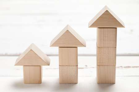 Wooden toy house on white table. This file is cleaned and retouched. Stock Photo