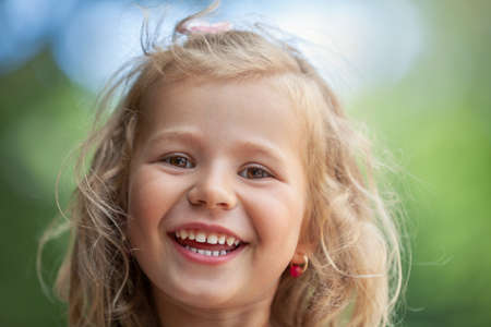 Smiling cute little girl on green background. This file is cleaned and retouched. Imagens