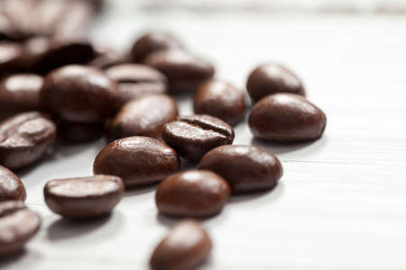 Close up of coffee beans on white table. This file is cleaned and retouched.