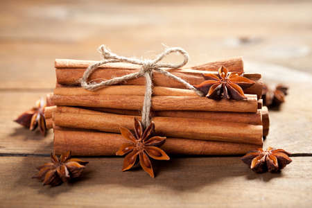 Close up of anise star and cinnamon stick on old wooden table. This file is cleaned and retouched.