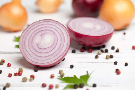 Sliced red onion with pepper on white table. This file is cleaned and retouched.
