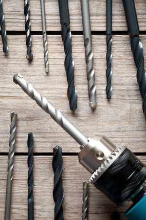 Close up of electric drill and drill bits on old wooden table. This file is cleaned and retouched.