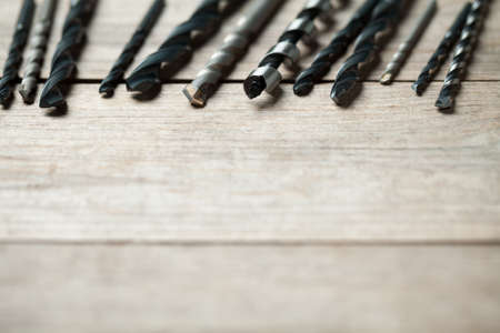 Close up of drill bits on old wooden table. At the bottom is empty space to put text or something else. This file is cleaned and retouched.