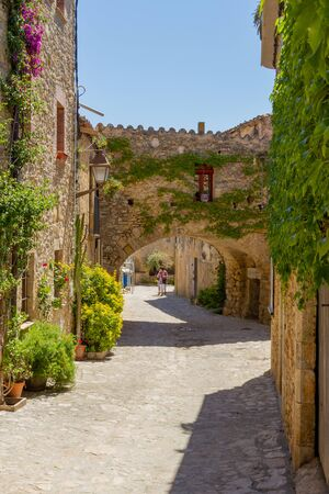 PERATALLADA, SPAIN - MAY 23, 2011: In the inland of Catelonia are very beautifull small and traditional vilages. Here a street with yellow stone houses and plants as decoration