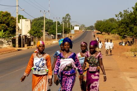 SANKANDI, GAMBIA- JAN 6, 2014: Once a month the doctor comes to town. Young woman with babies dress up for the occasion and walk together to have the monthly health checkup