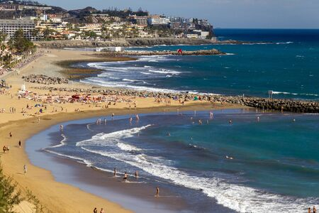 Tourists enjoying water and sun at the beaches of Playa del Ingles in Gran Canaria