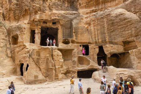 Little Petra, Jordan - Sept 20, 2013: Tourists visiting Little Petra, also known as Siq al-Barid, where buidings are carved in the mountains by the Nabataeans