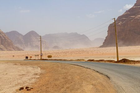 Road in the Wadi Rum desert with powerlines alongside and small signs beside the road. In the background the desert and mountains Zdjęcie Seryjne
