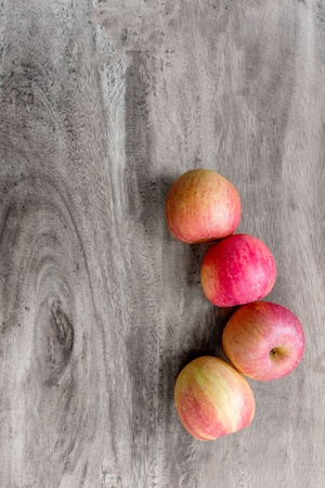Four apples on wooden table Stock Photo