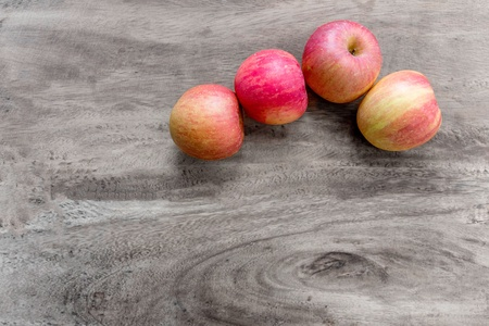 Four red apples on wooden table Stock Photo