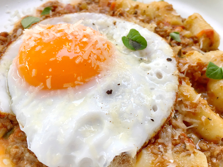 Over easy fried egg with cheese sprinkled on top of Italian food Stock Photo