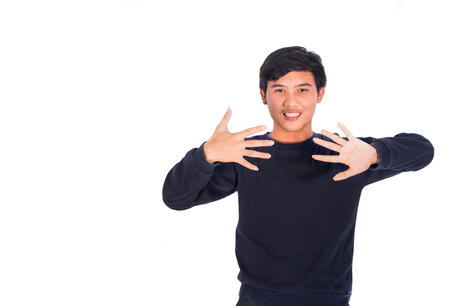 A handsome Asian man in black clothes standing shows ten fingers in Studio white background