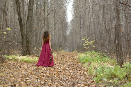 back ground: girl in a red dress walking in the forest Stock Photo