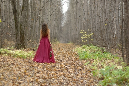 evening gowns: Female in a red dress walking in the forest Stock Photo