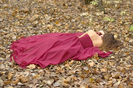 back ground: a girl in a red dress lying on the fallen leaves