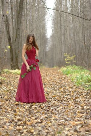 girl with a rose standing in the forest photo