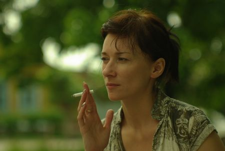 a woman smoking a cigarette outdoors