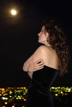 Girl in a black dress under full moon and city photo