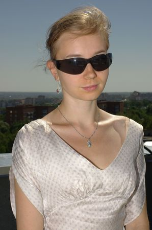 Girl in sunglasses wearing a silk blouse Stock Photo
