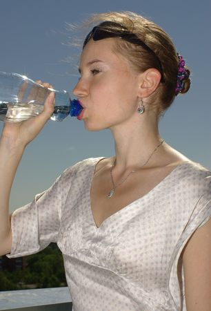 Female with sunglasses drinking water Stock Photo