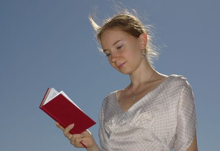 A girl reading a book with the red cover