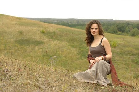 stole: Female with a red stole sitting in the field Stock Photo