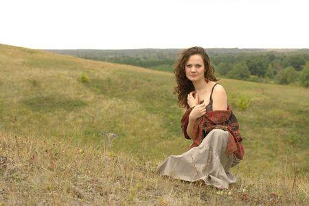 robo: Chica con una roja rob� sentado en el campo Foto de archivo