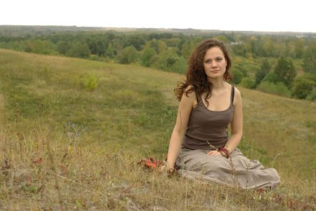 Female sitting in the autumn field Stock Photo