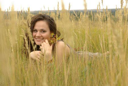 Pretty girl lying in the autumn field